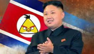 Kim Jung Un in front of new North Korean flag. He replaced the red star with 'Chuck,' the yellow Angry Bird.